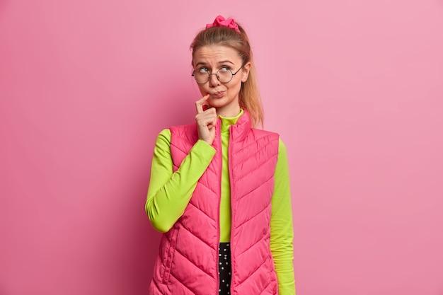 Nadenkende europese tienermeisje denkt na over idee, staat voor dilemma, ziet er onzeker en twijfelachtig uit, draagt een harde bril, groene trui, roze vest, denkt na over moeilijke vraag