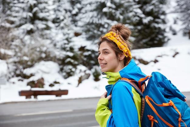Nadenkende europese vrouw gefocust opzij, wandelingen en trektochten in de buurt van besneeuwde bergen in de winter, geniet van landschap