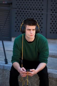 Nadenkende fronsende kerel met hoofdtelefoons
