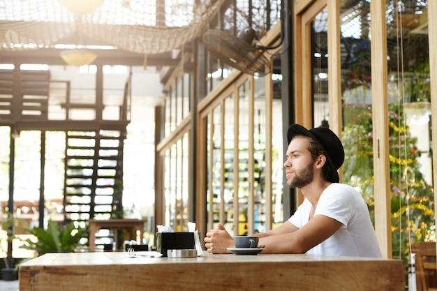 Nadenkende gebaarde kaukasische student die wit t-shirt en zwart hoofddeksel draagt die ochtendkoffie alleen heeft tijdens ontbijt