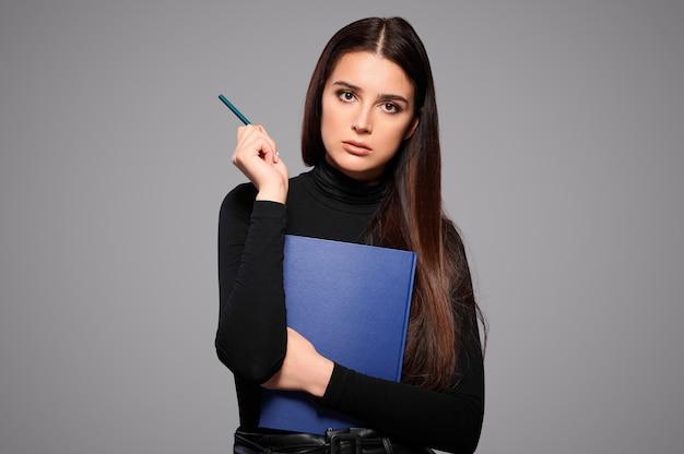 Nadenkende geconcentreerde drukke vrouw houdt potlood en blocnote, vrouwelijke student met een werkboek en pen, geïsoleerde achtergrond