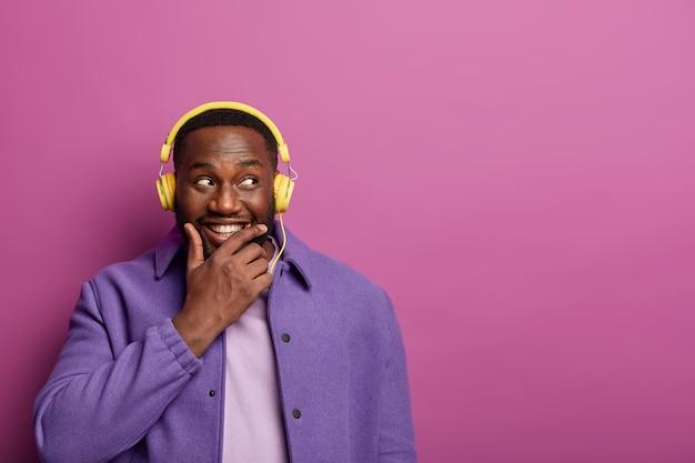 Nadenkende gelukkige man houdt kin vast, kocht een nieuwe koptelefoon om naar muziek te luisteren, kijkt opzij