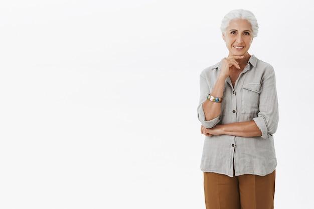 Nadenkende glimlachende grootmoeder die kijkt, keuze maakt