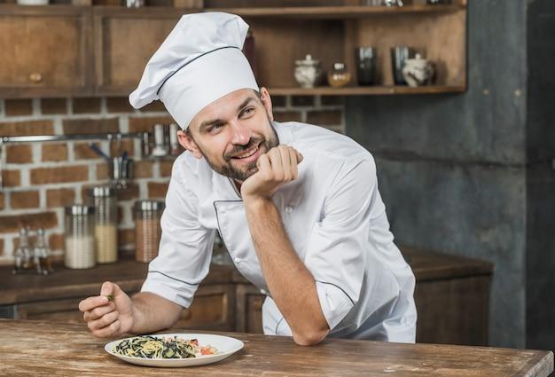 Nadenkende glimlachende mannelijke chef-kok die op de teller met een schotel in de keuken leunt