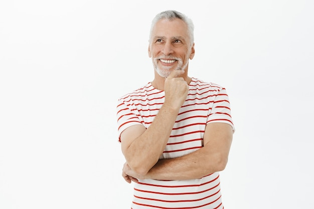 Nadenkende glimlachende oudere man op zoek naar de linkerbovenhoek met een blij gezicht