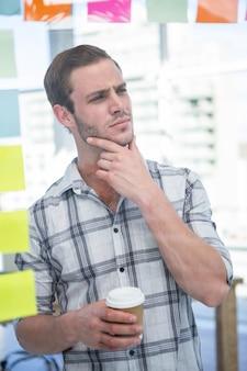Nadenkende hipstermens met koffie in bureau