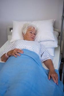 Nadenkende hogere patiënt die op bed ligt Premium Foto