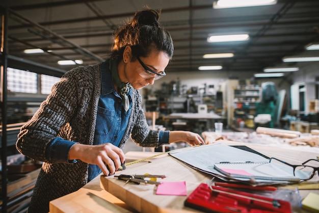Nadenkende industriële vrouwelijke ingenieur op middelbare leeftijd met oogglazen die met een meetlint in de workshop werken.