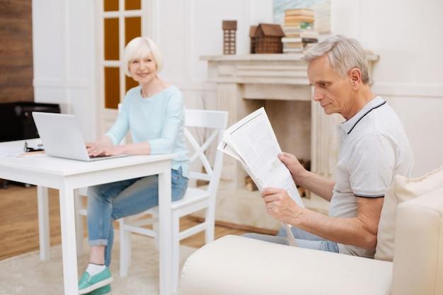 Nadenkende intelligente knappe man die op een bank in een woonkamer zit en een artikel leest terwijl zijn vrouw ergens aan werkt