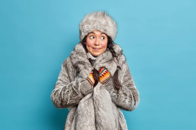 Nadenkende inuit-vrouw gekleed in grijze bontmuts en jas gebreide wanten draagt warme winterkleren geïsoleerd over blauwe studiomuur
