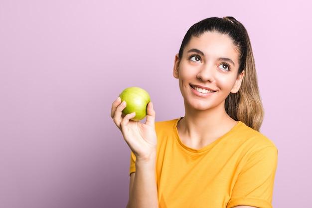 Nadenkende jonge aantrekkelijke vrouw in gele t-shirt die groene appel houdt en glimlachend denkend over ongezonde kost