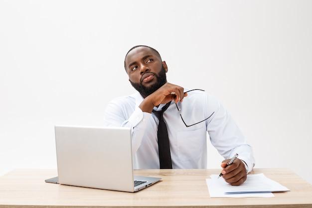 Nadenkende jonge afrikaanse amerikaanse zakenman die aan laptop computer werkt