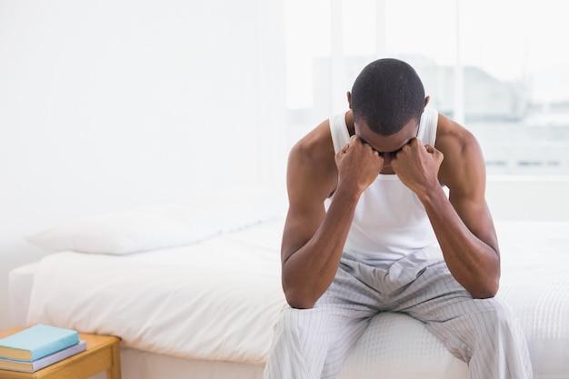 Nadenkende jonge afro-mensenzitting op bed
