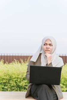 Nadenkende jonge aziatische moslimvrouw in groen kostuum en het werken aan een computer bij park. hand in de buurt van het gezicht.