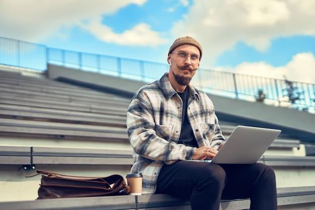 Nadenkende jonge, bebaarde man met snor werkt buiten terwijl hij zijn laptop op zijn benen houdt en zijwaarts kijkt