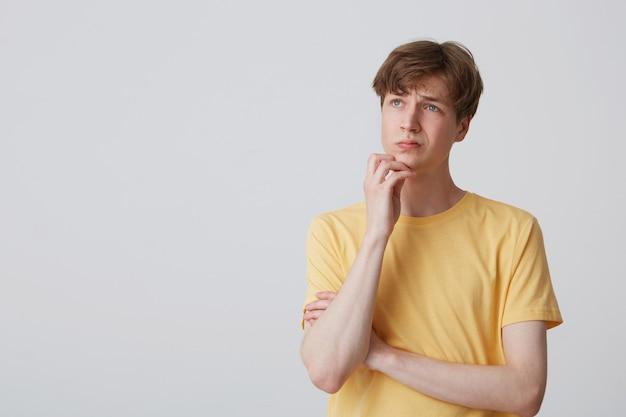 Nadenkende jonge blanke mannelijke student houdt zijn hand op de kin, draagt een geel, helder t-shirt, kijkt opzij met een geconcentreerde gezichtsuitdrukking en denkt na over zijn toekomst. geïsoleerd over witte muur