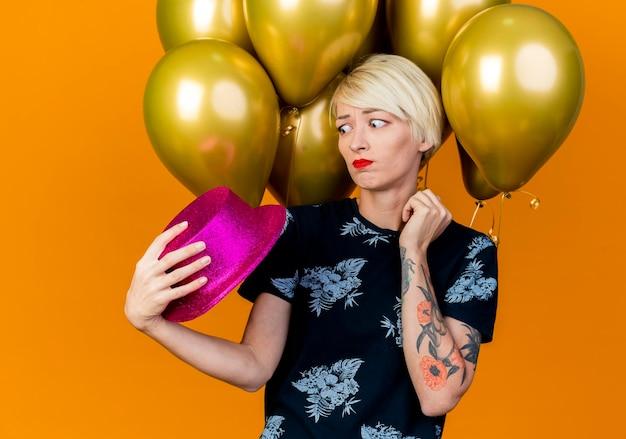 Nadenkende jonge blonde partijvrouw die zich voor ballons bevindt die en partijhoed bekijken die op oranje muur wordt geïsoleerd