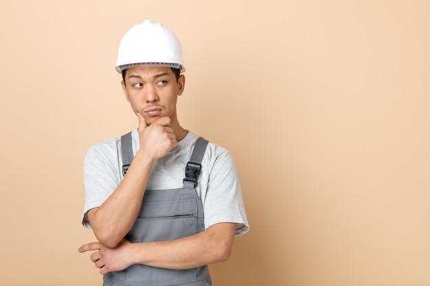 Nadenkende jonge bouwvakker die veiligheidshelm draagt en eenvormig hand op kin houdt die kant bekijkt