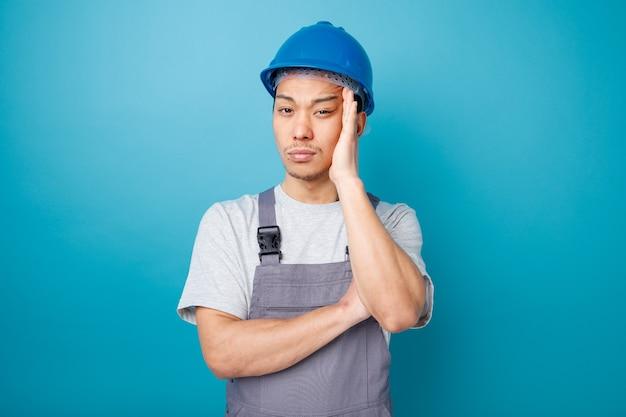 Nadenkende jonge bouwvakker die veiligheidshelm en uniform draagt die hand op hoofd houden