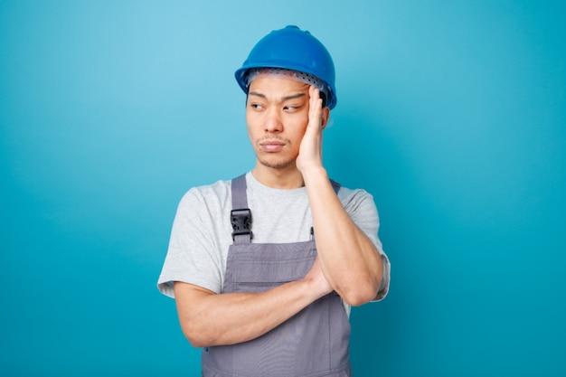 Nadenkende jonge bouwvakker die veiligheidshelm en uniform draagt ?? die hand op hoofd houdt die kant bekijkt