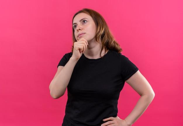 Nadenkende jonge casual vrouw met hand op kin en taille op geïsoleerde roze muur
