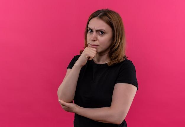 Nadenkende jonge casual vrouw met hand op kin op geïsoleerde roze muur met kopie ruimte
