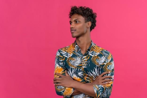 Nadenkende jonge donkere man met krullend haar in bladeren bedrukt overhemd hand in hand gevouwen en denken op een roze achtergrond