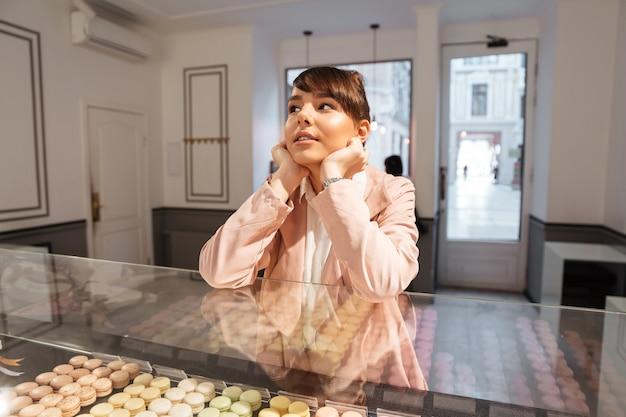 Nadenkende jonge jonge vrouw die gebakjes kiezen