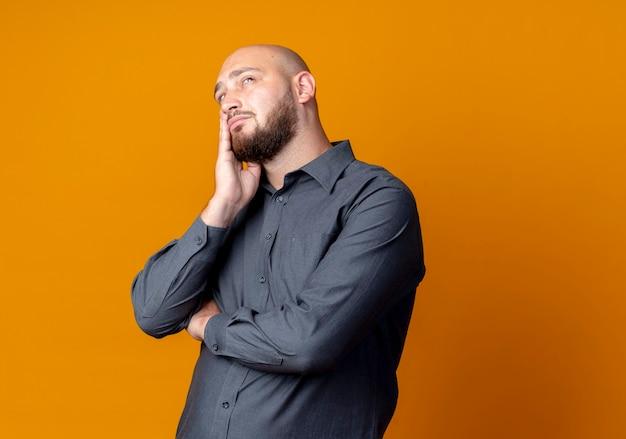 Nadenkende jonge kale callcentermens die met gesloten houding hand op gezicht zet die omhoog geïsoleerd op oranje muur kijkt