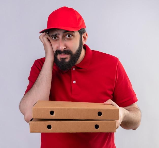 Nadenkende jonge knappe bezorger die rode uniform en pet draagt die pizzadozen houdt die recht kijkt en hand op wang legt die op witte muur wordt geïsoleerd