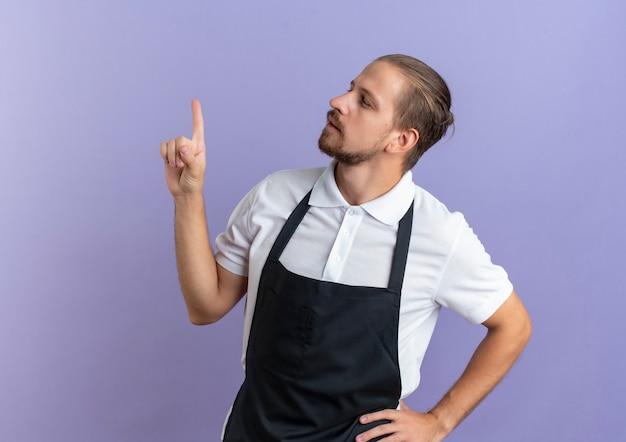 Nadenkende jonge knappe kapper die eenvormig draagt die hand op taille zet en vinger opheft die kant bekijkt die op purpere muur wordt geïsoleerd