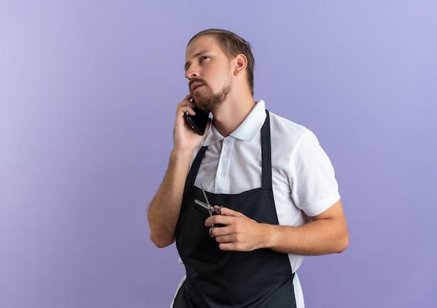 Nadenkende jonge knappe kapper die uniform draagt ?? die op telefoon spreekt die omhoog kijkt en schaar houdt die op purpere muur wordt geïsoleerd