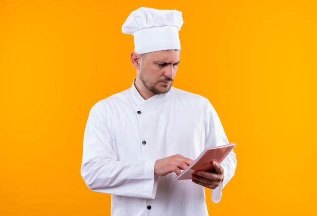 Nadenkende jonge knappe kok in de blocnote van de chef-kok eenvormige holding die hand zet en het bekijkt geïsoleerd op oranje ruimte