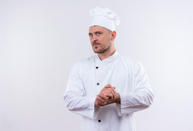 Nadenkende jonge knappe kok in eenvormige chef-kok die handen op geïsoleerde witte ruimte samenhoudt