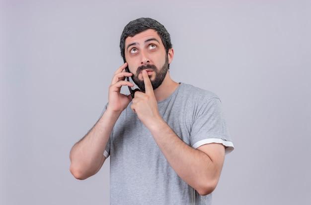Nadenkende jonge knappe man praten over de telefoon vinger op de lippen te zetten en opzoeken geïsoleerd op een witte muur