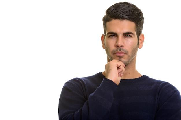 Nadenkende jonge knappe perzische man met de hand op de kin