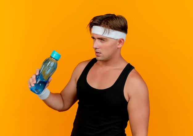 Nadenkende jonge knappe sportieve man die hoofdband en polsbandjes draagt die waterfles houden die recht kijkt geïsoleerd op oranje muur