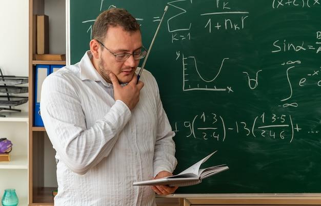 Nadenkende jonge leraar die een bril draagt die voor het schoolbord in de klas staat en de hand op de kin houdt met de aanwijzer die het notitieblok leest
