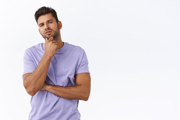Nadenkende jonge man die iets in de winkel plukt, kin peinzend loensend aanraakt, overweegt welke keuze het beste is, mening vormt, oordeel uitspreekt, variant plukken, nadenken over witte muur