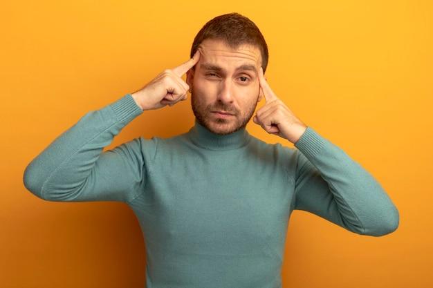 Nadenkende jonge man die voorzijde doet denken gebaar geïsoleerd op oranje muur kijken
