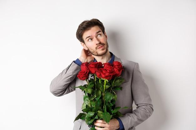 Nadenkende jonge man in pak gaande valentijnsdag datum, boeket rozen, denken en krabben hoofd, staande tegen een witte achtergrond te houden.