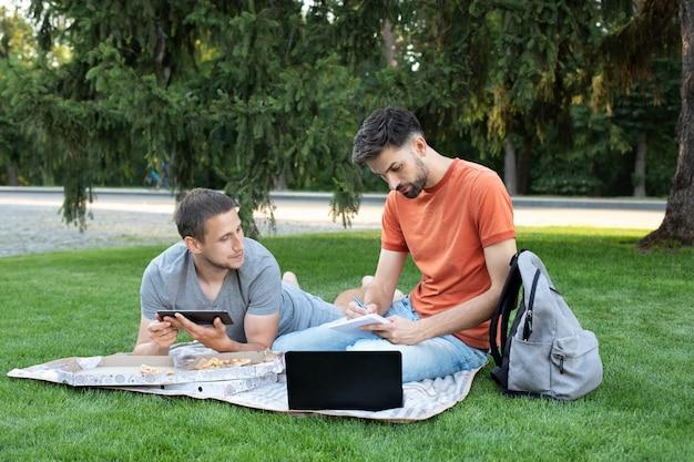 Nadenkende jonge man zit met een laptop op gras op een universiteitscampus en maakt aantekeningen in notitieblok. man iets uit te leggen aan haar vriend in laptop.