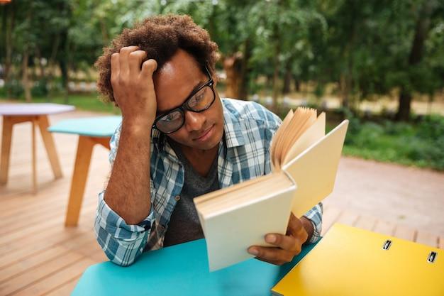 Nadenkende jonge man zitten en lezen van boek buitenshuis