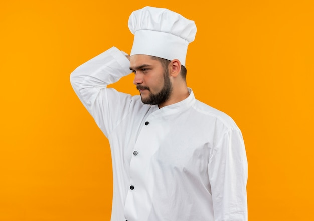 Nadenkende jonge mannelijke kok die in eenvormige chef-kok hand achter hoofd zet die kant bekijkt die op oranje ruimte wordt geïsoleerd