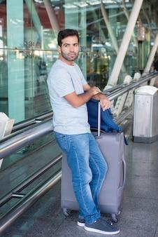Nadenkende jonge mens die op metaaltraliewerk bij luchthaven leunt