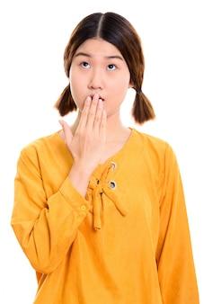 Nadenkende jonge mooie aziatische vrouw die geschokt kijkt