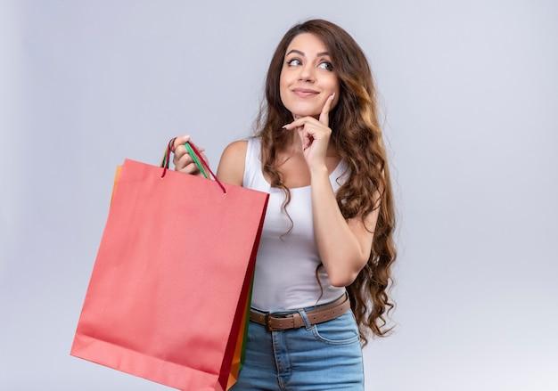 Nadenkende jonge mooie boodschappentassen van de meisjesholding die rechterkant met vinger op wang op geïsoleerde witte muur bekijken