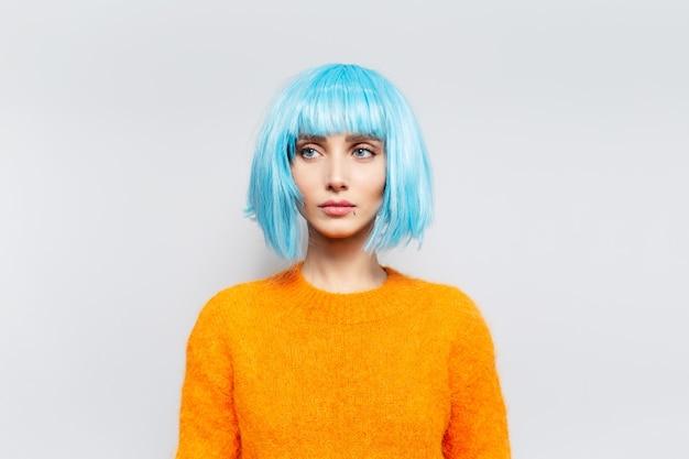 Nadenkende jonge mooie vrouw met blauw haar in oranje sweater tegen witte muur.