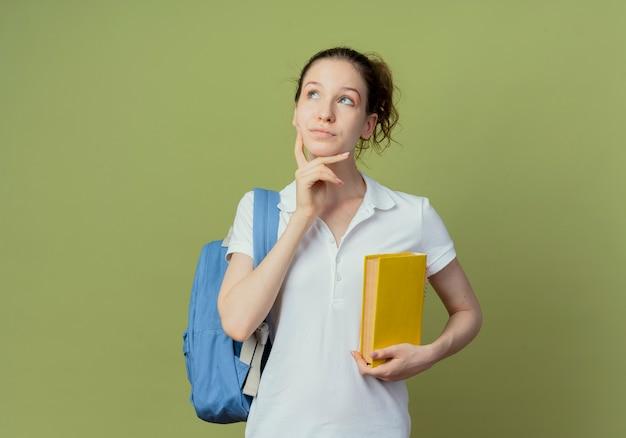 Nadenkende jonge mooie vrouwelijke student die het boek van de achterzakholding draagt ?? die omhoog kijkt en kin aanraakt die op groene achtergrond met exemplaarruimte wordt geïsoleerd