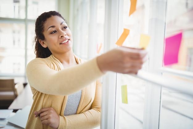 Nadenkende jonge onderneemster die zelfklevende nota's in creatief bureau bekijken
